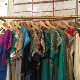 A close-up of beautifully embroidered tunics displayed at the Tail of the Yak Boutique.