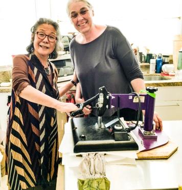 Instructors Yoshiko and Elisa working the heat press